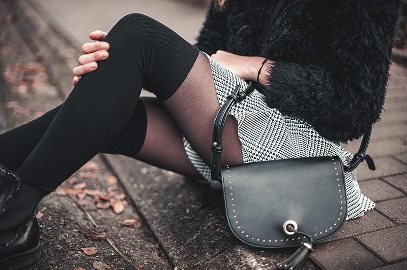 Tenue avec la jupe en imprimé prince de galles photographiée sur le pas de la porte. Ici, on voit les détails du sac en bandouillère.