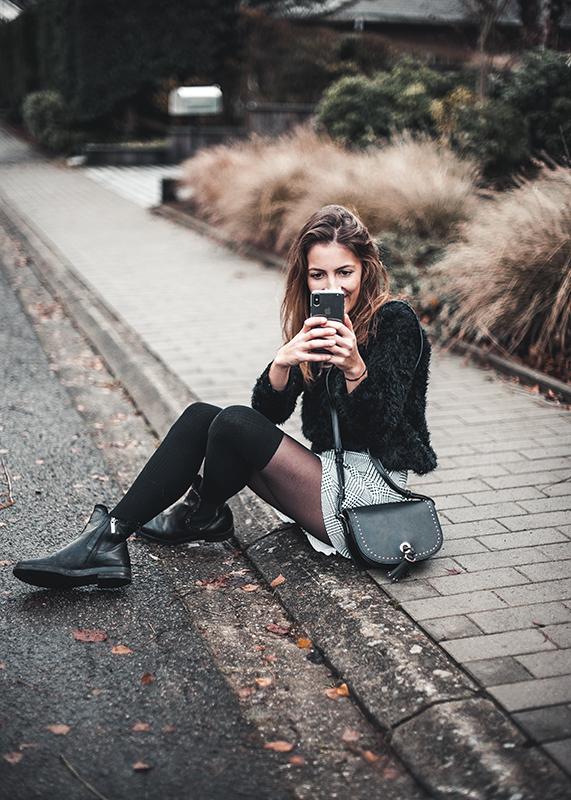 Photographie assise sur le trottoir. Tenue avec jupe en imprimé prince de galles.