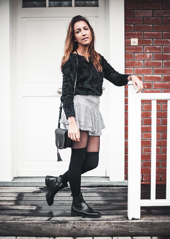 Tenue avec la jupe en imprimé prince de galles photographiée sur le pas de la porte.